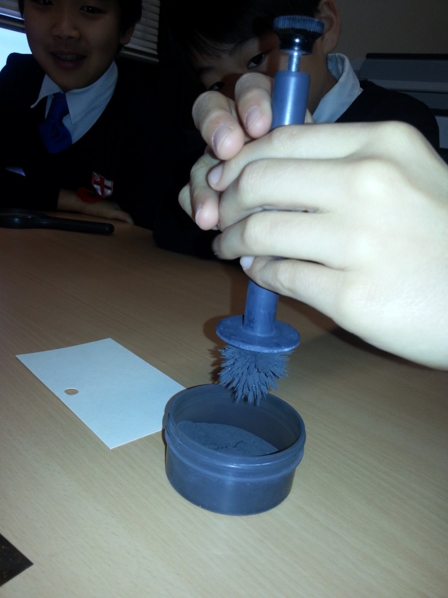 The magnetic wand for applying dust to prints. The metal components of the dust is attracted to the application end.